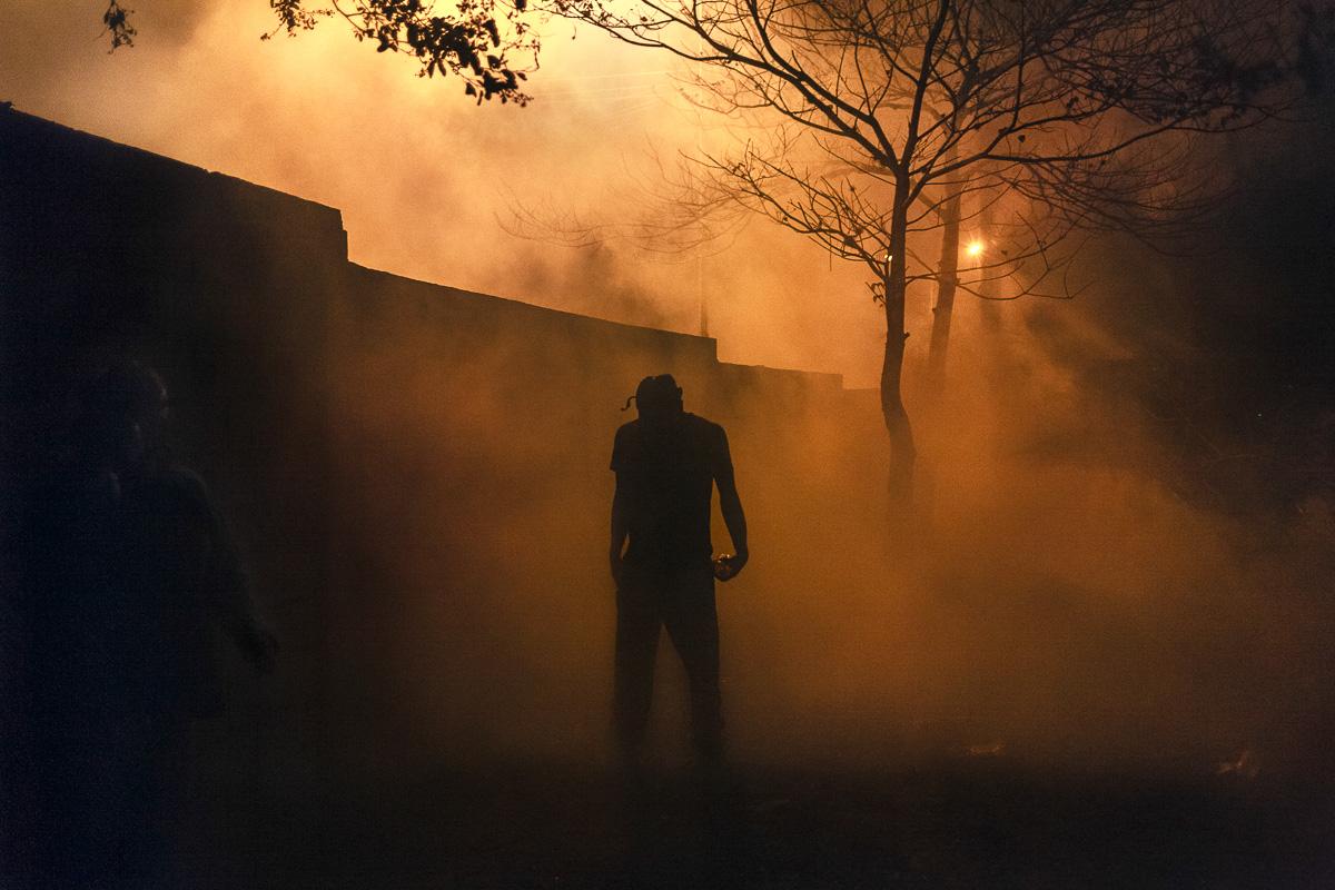 En la noche del 27 de febrero de 2015, un manifestante se detiene en medio de una nube de gas lacrimógeno. Del otro lado del muro, las fuerzas de seguridad intentaron recuperar el control de la Universidad de Los Andes en San Cristobal, Estado Táchira. El conflicto duró más de cuatro horas esa noche.