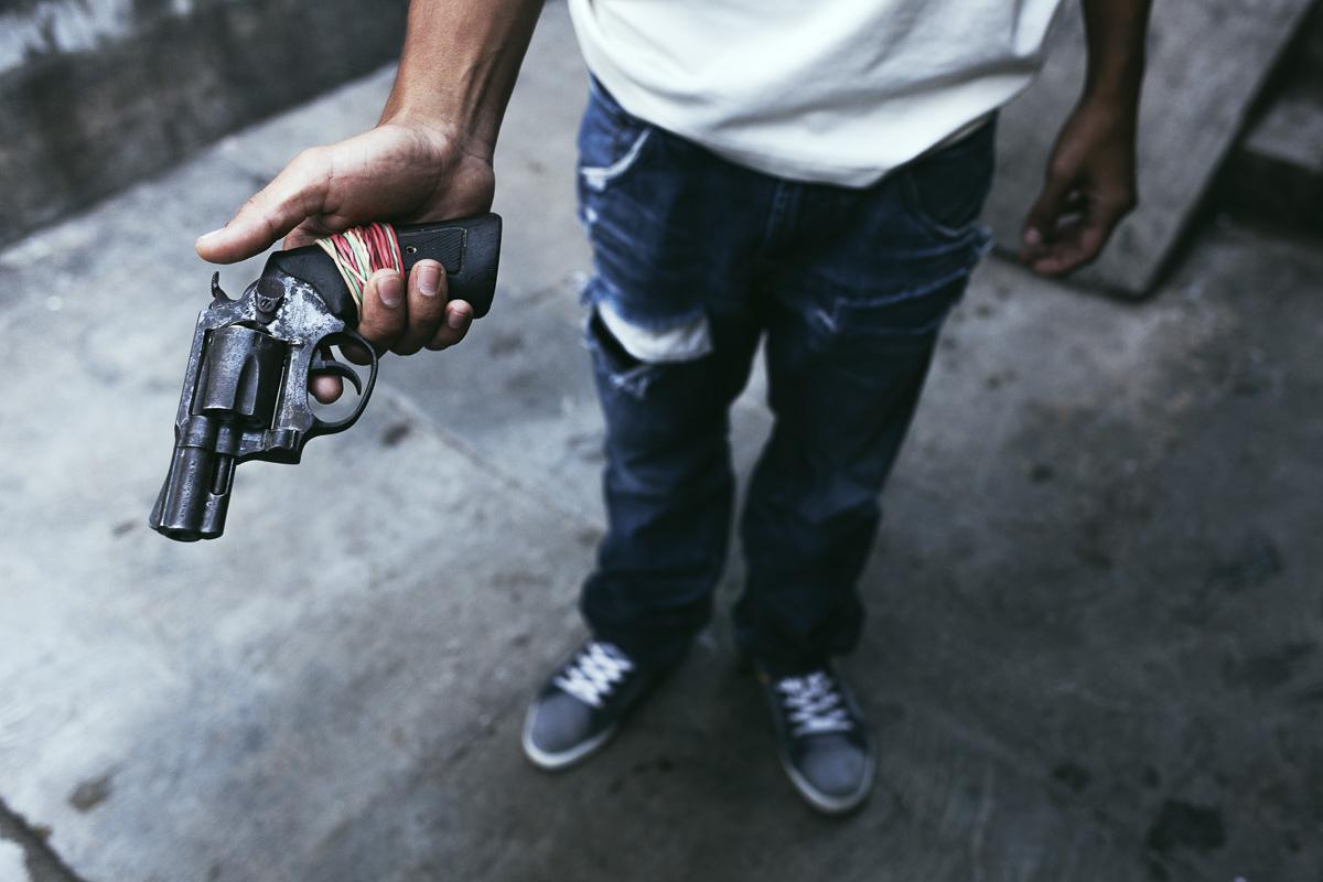"""En el barrio de Artigas, en Caracas, un joven sostiene un revólver cargado. Él comparte el arma con un par de amigos. """"Es más fácil encontrar armas que encontrar pan"""", dijo el joven riendo. Para Noviembre de 2015, las manifestaciones masivas ya habían pasado, aunque no en vano: dejaron una imagen clara de cuán letal era la ciudad. Debajo de la imagen, quedó una cicatriz en la conciencia colectiva. A medida que la economía se derrumbó y la violencia alcanzó su punto máximo, Caracas se convirtió en una capital feroz. El gobierno no sabe cuántas armas ilegales hay actualmente en el país, perdió el control sobre el asunto. En 2009, Amnistía Internacional advirtió que Venezuela podría tener hasta 6 millones de armas ilegales. Números más conservadores, como el proporcionado por la Comisión Presidencial para el Control de Armas, Municiones y Desmantelamiento en 2012, cita 1.2 a 1.5 millones de armas no registradas. Eso es en un país de 30 millones de habitantes. Frente a esta realidad, cada quién trató de obtener algún tipo de control sobre su vidas y, a medida que la economía formal colapsaba, la economía ilegal crecía. Los jóvenes de todos los estratos económicos se involucraron cada vez más con el tráfico de drogas, armas, el secuestro o el mercado negro de divisas. Las pistolas infestaron las calles. En promedio, 60 personas mueren diariamente en Venezuela."""