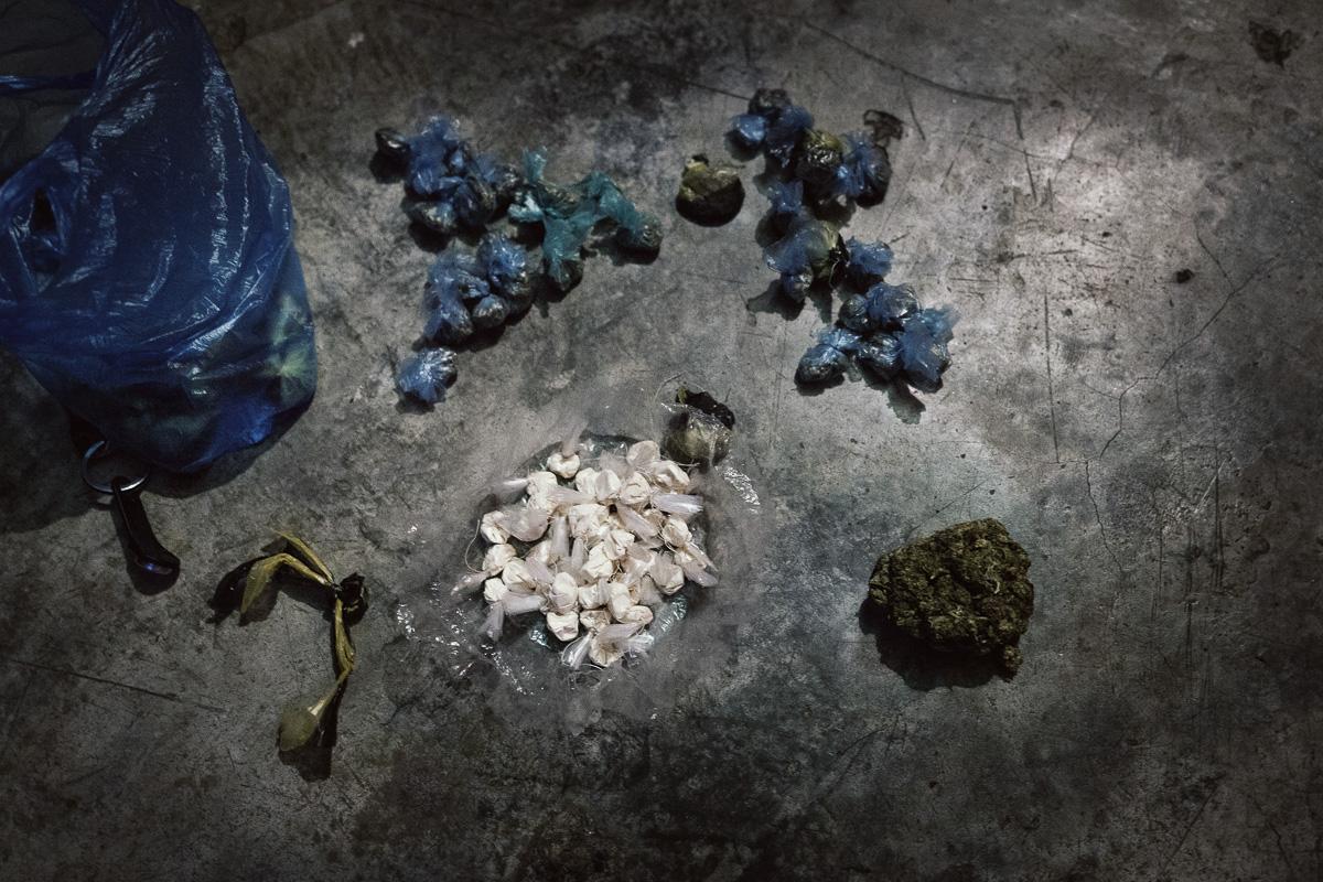 Un joven cuenta su botin de drogas: más de una docena de bolsas de cocaína y marihuana. Se gana la vida vendiendo drogas en un barrio al oeste de Caracas. Lo que gana apenas es suficiente para pagar el creciente costo de la vida. Para Noviembre de 2015, las manifestaciones masivas ya habían pasado, aunque no en vano: dejaron una imagen clara de cuán letal era la ciudad. Debajo de la imagen, quedó una cicatriz en la conciencia colectiva. A medida que la economía se derrumbó y la violencia alcanzó su punto máximo, Caracas se convirtió en una capital feroz. El gobierno no sabe cuántas armas ilegales hay actualmente en el país, perdió el control sobre el asunto. En 2009, Amnistía Internacional advirtió que Venezuela podría tener hasta 6 millones de armas ilegales. Números más conservadores, como el proporcionado por la Comisión Presidencial para el Control de Armas, Municiones y Desmantelamiento en 2012, cita 1.2 a 1.5 millones de armas no registradas. Eso es en un país de 30 millones de habitantes. Frente a esta realidad, cada quién trató de obtener algún tipo de control sobre su vidas y, a medida que la economía formal colapsaba, la economía ilegal crecía. Los jóvenes de todos los estratos económicos se involucraron cada vez más con el tráfico de drogas, armas, el secuestro o el mercado negro de divisas. Las pistolas infestaron las calles. En promedio, 60 personas mueren diariamente en Venezuela.