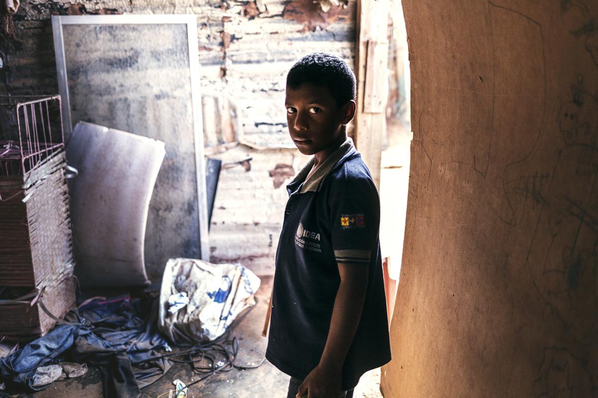 Un niño de diez años se para sobre los restos de su casa. Fue saqueada y desmantelada en la mañana del 25 de julio de 2016. Esta operación dejó a más de 200 familias sin casa. La familia Osorio fue una ellas. El niño es uno de cada nueve menores de edad que vivían en la pequeña casa, hecha de cartón y planchas de zinc. Los desalojos masivos comenzaron a las 3 a.m., cuando varias agencias policiales allanaron la pequeña barriada, ubicada en las afueras de Caracas. Según Nicolás Maduro, los allanamientos buscaban acabar con bandas criminales y paramilitares, sin embargo, nadie fue acusado públicamente como resultado de estos allanamientos.