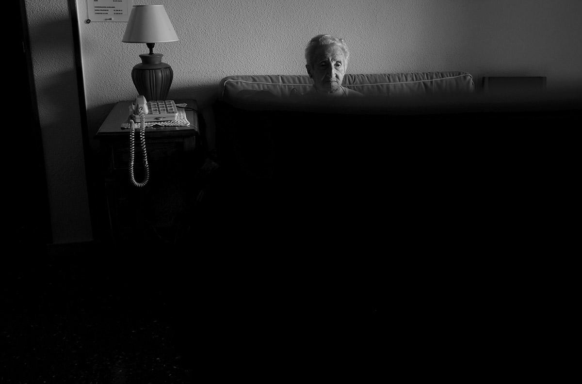 """María viendo la televisión. La soledad de María contra la Ley de Dependencia María del Palacio vive en soledad. Viuda y con 96 años no puede abandonar su piso de Madrid. Sufre pérdidas de memoria y serios problemas que le impiden moverse con autonomía. Es dependiente y necesita ayuda y atención. A pesar de su estado, la Comunidad de Madrid no le autoriza el traslado urgente a una residencia pública: """"Puede andar sola y comer con sus manos"""", justifican las autoridades. Como María, miles de personas de avanzada edad sufren psíquica y físicamente las consecuencias del aislamiento al que se ven inducidas. Sus familias, sobre las que recae el esfuerzo, también se quedan indefensas. Este es un tributo al esfuerzo de María y al de tantos ancianos que, a su edad, padecen el desamparo del Estado. Este reportaje ha sido realizado íntegramente en el interior del domicilio de María del Palacio en calle Ervigio, distrito de Carabanchel, Madrid, Comunidad Autónoma de Madrid, España; en el seguimiento de sus actividades cotidianas y con su autorización, entre los meses de Agosto y Diciembre de 2016. Cuando puede andar, va a comer al comedor social cercano a su casa. ©Carlos de Andres/ Getty Images. 2016"""