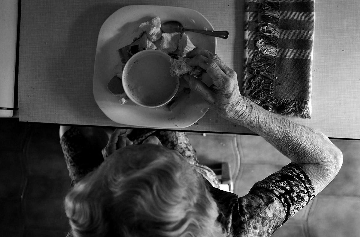 """María durante el desayuno. La soledad de María contra la Ley de Dependencia María del Palacio vive en soledad. Viuda y con 96 años no puede abandonar su piso de Madrid. Sufre pérdidas de memoria y serios problemas que le impiden moverse con autonomía. Es dependiente y necesita ayuda y atención. A pesar de su estado, la Comunidad de Madrid no le autoriza el traslado urgente a una residencia pública: """"Puede andar sola y comer con sus manos"""", justifican las autoridades. Como María, miles de personas de avanzada edad sufren psíquica y físicamente las consecuencias del aislamiento al que se ven inducidas. Sus familias, sobre las que recae el esfuerzo, también se quedan indefensas. Este es un tributo al esfuerzo de María y al de tantos ancianos que, a su edad, padecen el desamparo del Estado. Este reportaje ha sido realizado íntegramente en el interior del domicilio de María del Palacio en calle Ervigio, distrito de Carabanchel, Madrid, Comunidad Autónoma de Madrid, España; en el seguimiento de sus actividades cotidianas y con su autorización, entre los meses de Agosto y Diciembre de 2016. Cuando puede andar, va a comer al comedor social cercano a su casa. ©Carlos de Andres/ Getty Images. 2016"""