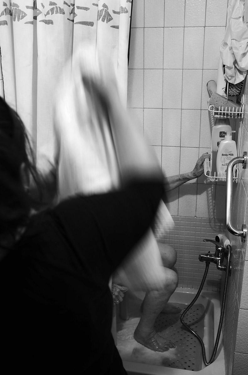 """Baño diario. La soledad de María contra la Ley de Dependencia María del Palacio vive en soledad. Viuda y con 96 años no puede abandonar su piso de Madrid. Sufre pérdidas de memoria y serios problemas que le impiden moverse con autonomía. Es dependiente y necesita ayuda y atención. A pesar de su estado, la Comunidad de Madrid no le autoriza el traslado urgente a una residencia pública: """"Puede andar sola y comer con sus manos"""", justifican las autoridades. Como María, miles de personas de avanzada edad sufren psíquica y físicamente las consecuencias del aislamiento al que se ven inducidas. Sus familias, sobre las que recae el esfuerzo, también se quedan indefensas. Este es un tributo al esfuerzo de María y al de tantos ancianos que, a su edad, padecen el desamparo del Estado. Este reportaje ha sido realizado íntegramente en el interior del domicilio de María del Palacio en calle Ervigio, distrito de Carabanchel, Madrid, Comunidad Autónoma de Madrid, España; en el seguimiento de sus actividades cotidianas y con su autorización, entre los meses de Agosto y Diciembre de 2016. Cuando puede andar, va a comer al comedor social cercano a su casa."""