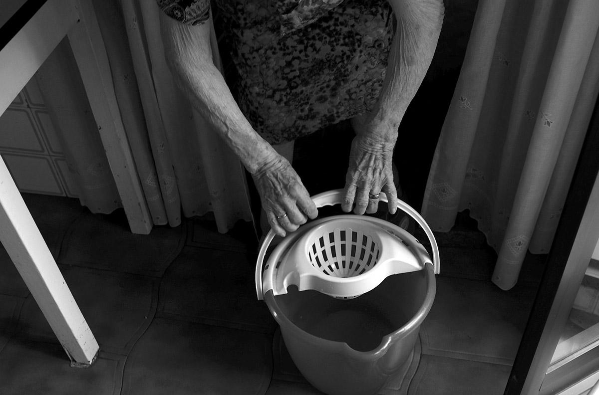 """Preparando el cubo de agua. La soledad de María contra la Ley de Dependencia María del Palacio vive en soledad. Viuda y con 96 años no puede abandonar su piso de Madrid. Sufre pérdidas de memoria y serios problemas que le impiden moverse con autonomía. Es dependiente y necesita ayuda y atención. A pesar de su estado, la Comunidad de Madrid no le autoriza el traslado urgente a una residencia pública: """"Puede andar sola y comer con sus manos"""", justifican las autoridades. Como María, miles de personas de avanzada edad sufren psíquica y físicamente las consecuencias del aislamiento al que se ven inducidas. Sus familias, sobre las que recae el esfuerzo, también se quedan indefensas. Este es un tributo al esfuerzo de María y al de tantos ancianos que, a su edad, padecen el desamparo del Estado. Este reportaje ha sido realizado íntegramente en el interior del domicilio de María del Palacio en calle Ervigio, distrito de Carabanchel, Madrid, Comunidad Autónoma de Madrid, España; en el seguimiento de sus actividades cotidianas y con su autorización, entre los meses de Agosto y Diciembre de 2016. Cuando puede andar, va a comer al comedor social cercano a su casa. ©Carlos de Andres/ Getty Images. 2016"""