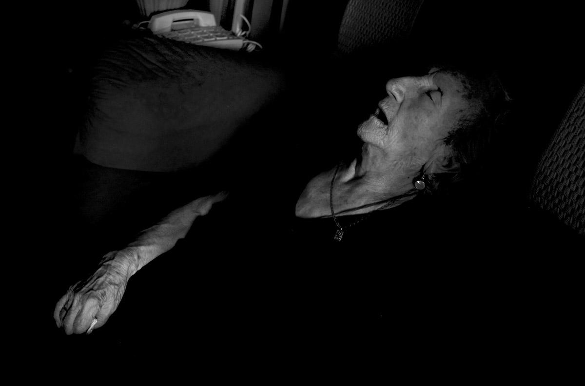"""La siesta. La soledad de María contra la Ley de Dependencia María del Palacio vive en soledad. Viuda y con 96 años no puede abandonar su piso de Madrid. Sufre pérdidas de memoria y serios problemas que le impiden moverse con autonomía. Es dependiente y necesita ayuda y atención. A pesar de su estado, la Comunidad de Madrid no le autoriza el traslado urgente a una residencia pública: """"Puede andar sola y comer con sus manos"""", justifican las autoridades. Como María, miles de personas de avanzada edad sufren psíquica y físicamente las consecuencias del aislamiento al que se ven inducidas. Sus familias, sobre las que recae el esfuerzo, también se quedan indefensas. Este es un tributo al esfuerzo de María y al de tantos ancianos que, a su edad, padecen el desamparo del Estado. Este reportaje ha sido realizado íntegramente en el interior del domicilio de María del Palacio en calle Ervigio, distrito de Carabanchel, Madrid, Comunidad Autónoma de Madrid, España; en el seguimiento de sus actividades cotidianas y con su autorización, entre los meses de Agosto y Diciembre de 2016. Cuando puede andar, va a comer al comedor social cercano a su casa. ©Carlos de Andres/ Getty Images. 2016"""