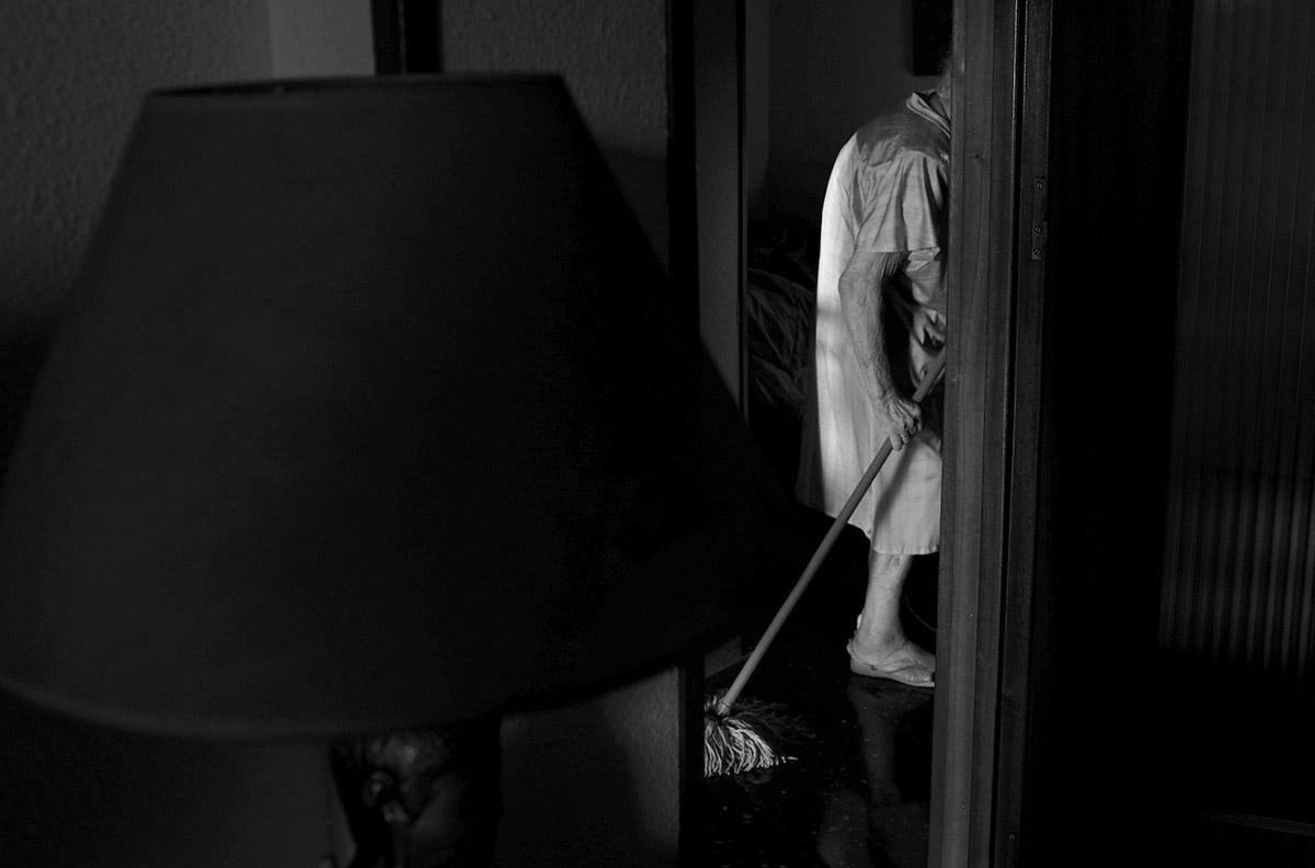"""Fregando el suelo. La soledad de María contra la Ley de Dependencia María del Palacio vive en soledad. Viuda y con 96 años no puede abandonar su piso de Madrid. Sufre pérdidas de memoria y serios problemas que le impiden moverse con autonomía. Es dependiente y necesita ayuda y atención. A pesar de su estado, la Comunidad de Madrid no le autoriza el traslado urgente a una residencia pública: """"Puede andar sola y comer con sus manos"""", justifican las autoridades. Como María, miles de personas de avanzada edad sufren psíquica y físicamente las consecuencias del aislamiento al que se ven inducidas. Sus familias, sobre las que recae el esfuerzo, también se quedan indefensas. Este es un tributo al esfuerzo de María y al de tantos ancianos que, a su edad, padecen el desamparo del Estado. Este reportaje ha sido realizado íntegramente en el interior del domicilio de María del Palacio en calle Ervigio, distrito de Carabanchel, Madrid, Comunidad Autónoma de Madrid, España; en el seguimiento de sus actividades cotidianas y con su autorización, entre los meses de Agosto y Diciembre de 2016. Cuando puede andar, va a comer al comedor social cercano a su casa. ©Carlos de Andres/ Getty Images. 2016"""