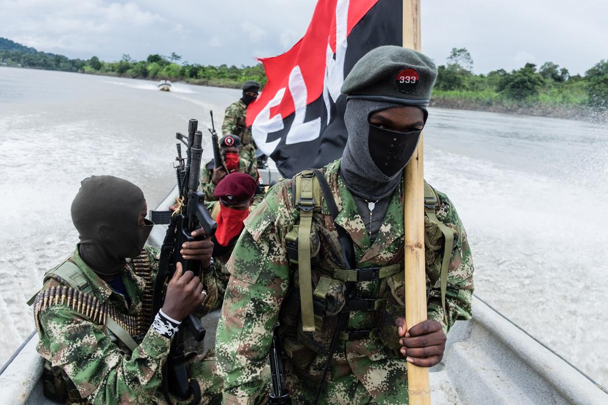Guerrilleros del ELN, en camino a la liberación de un miembro del grupo paramilitar Autodefensas Gaitanistas de Colombia a lo largo del río San Juan en el departamento de Chocó.