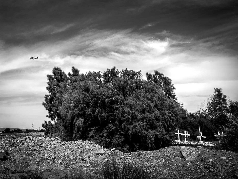 Helicóptero Sikorsky UH-60 Black Hawk de combate del US Border Patrol, sobrevuela la frontera junto al rio Colorado en labores de vigilancia de la frontera con México, cerca de Yuma, Arizona. En el mismo lugar, una fosa común alberga los cuerpos de migrantes irregulares sin identificar. El paso de sur a norte a costado 10.000 muertes desde 1994, año del inicio de la construcción del muro. 15 de Abril de 2017. © Miguel Cerezo.