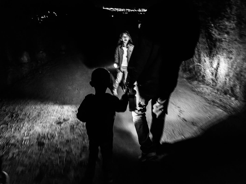 Una familia de irregulares acompañada de sus hijos pequeños, se desplaza junto al muro, en medio de la noche, en algún lugar indeterminado entre Mexicali y Tecate en Mexico. 6 de Noviembre de 2016. © Miguel Cerezo.