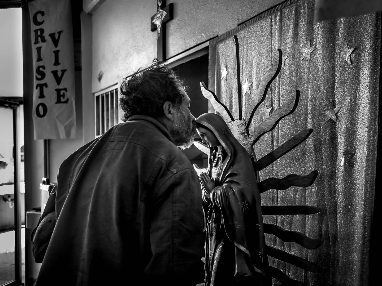 Usuario agradece a la virgen los alimentos recibidos en el desayunador salesiano del Padre Chava. Esta institución benéfica y gestionada por voluntarios, reparte 1500 comidas y dispensa aseo y ropa a unas 250 personas diariamente, según los recursos disponibles. Son en la mayoria de los casos, los propios ciudadanos de Tijuana ( jubilados , estudiantes, trabajadores y amas de casa ), los que voluntariamente brindan apoyo a estas personas desamparadas y que viven en la calle. Tijuana, Baja California, México. 18 de Abril de 2017. © Miguel Cerezo.