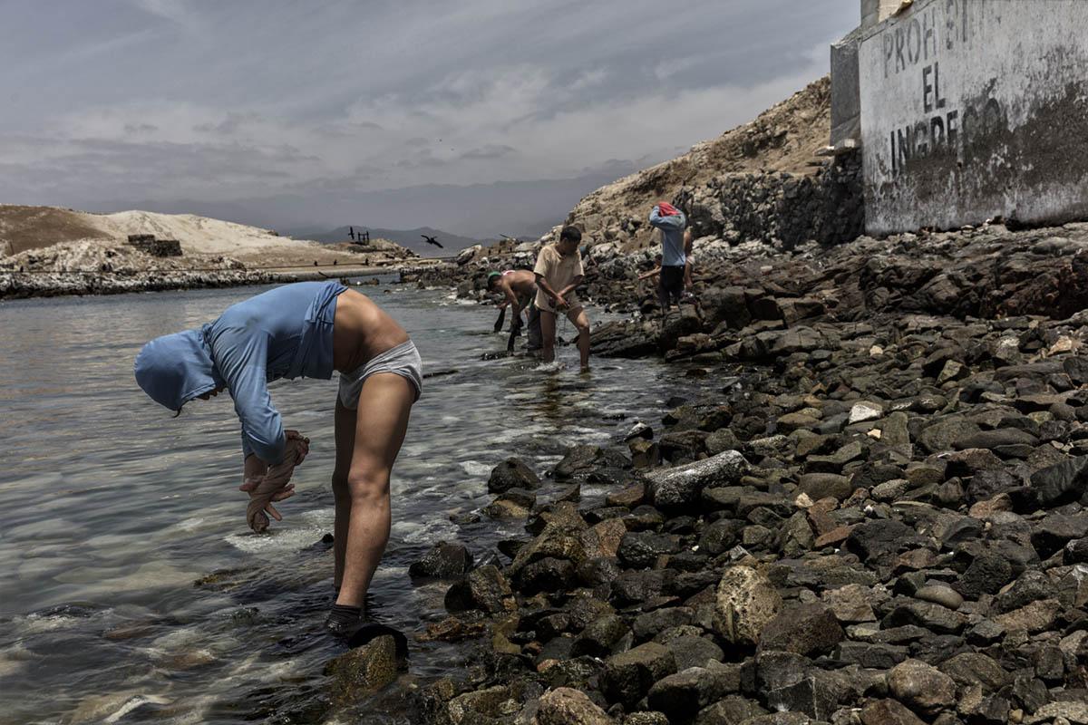 Isla Asia - Perú 2017: Un trabajador se baña en el mar tras acabar su jornada de trabajo en la isla.
